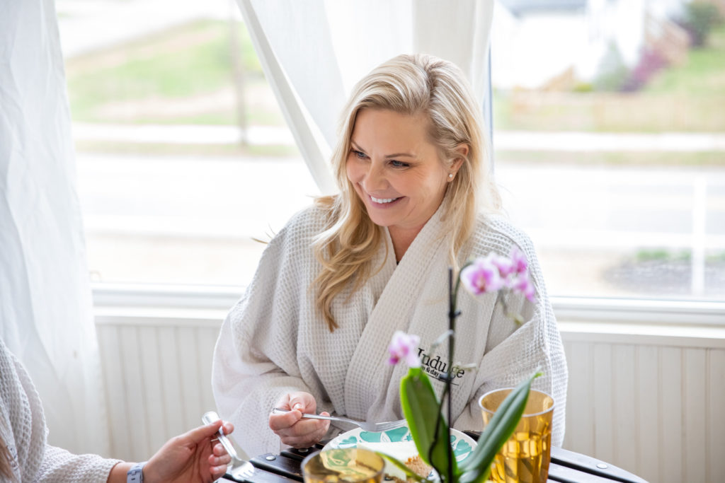 smiling woman in bathrobe sitting at a table eating